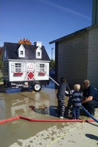 Fireman helping children use a fire hose to put out fire in practice drill