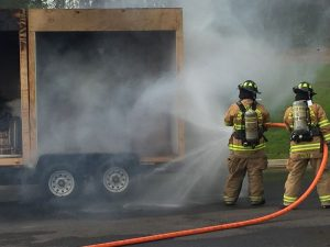 Two firefighters extinguishing a smoking truck
