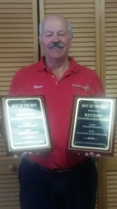 DKI employee holding two Bouchard Awards