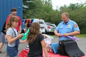 Policeman making balloon animals for children at event