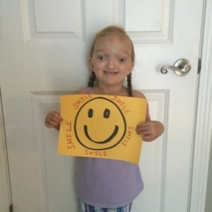 AIR Run for a Reason child holding up a sign with a smiley face
