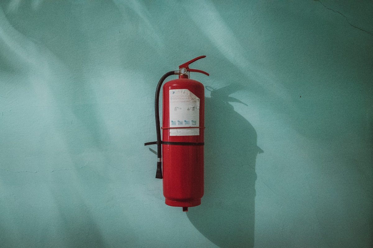 Fire Extinguisher mounted on blue wall