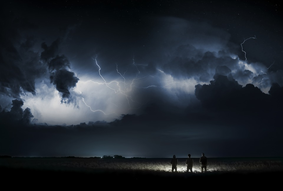 Lightning storm in a field with three people watching