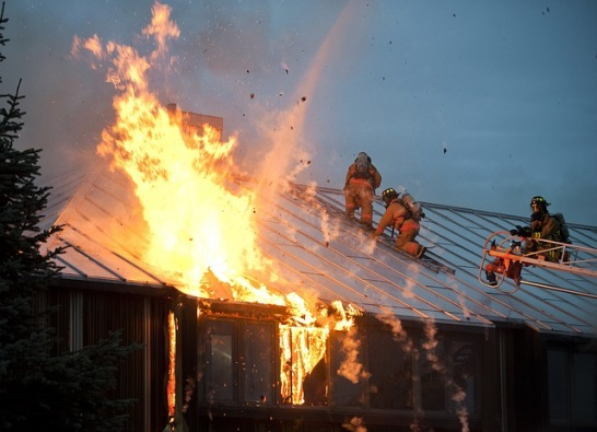 Firefighters on rooftop extinguishing a fire