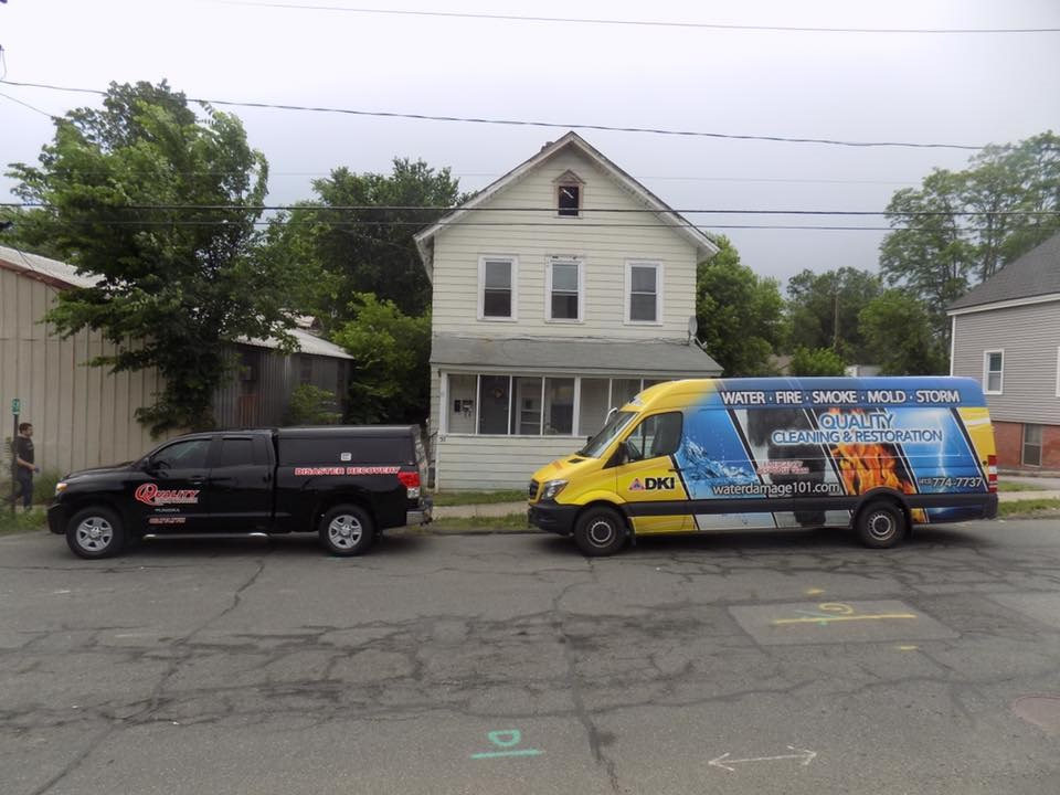 DKI Quality Cleaning and Restoration truck in front of a damaged home