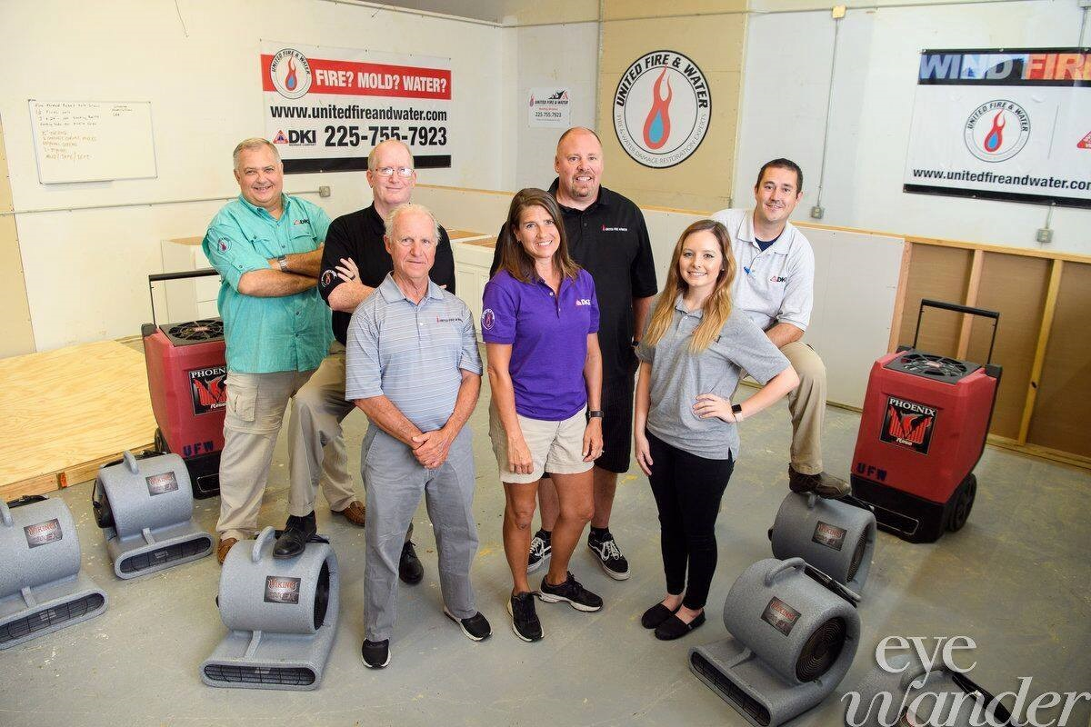 DKI members posing for a picture with floor drying vacuums