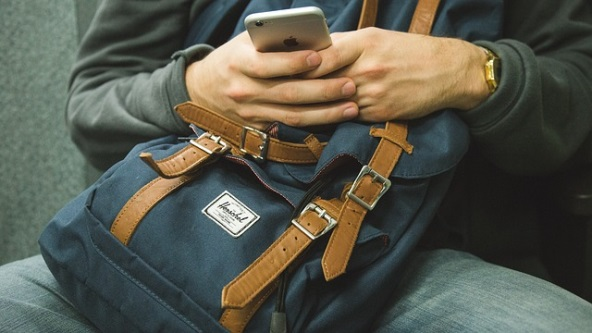 Person on their phone while holding a bag in their lap