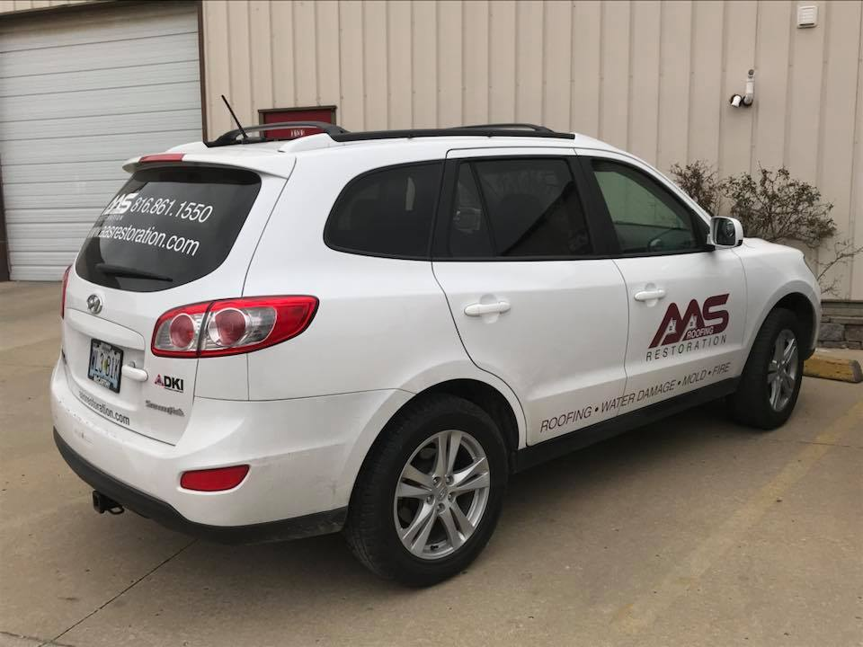 AAS Restoration service car in front of a business