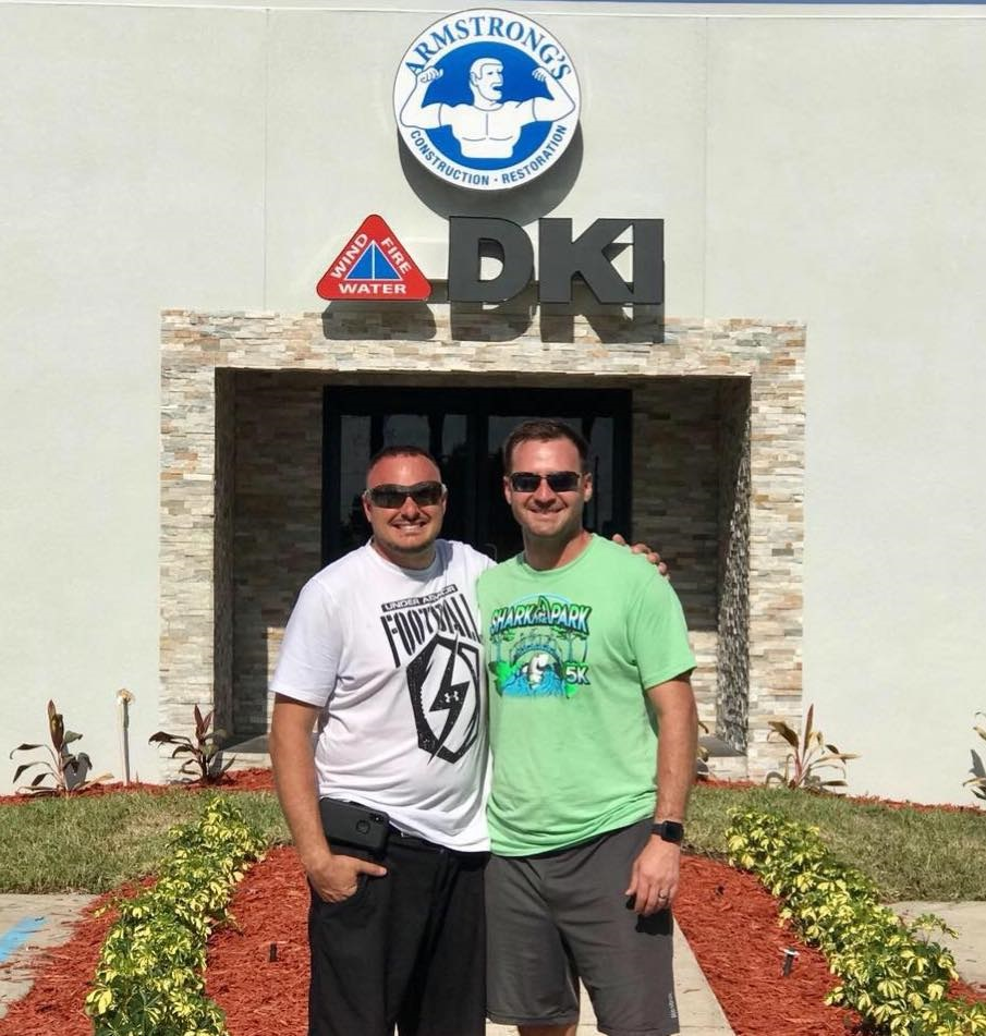 Two DKI members posing for a picture in front of DKI Armstrong's business