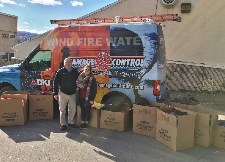 Damage Control members standing in front of service truck surrounded by donation boxes