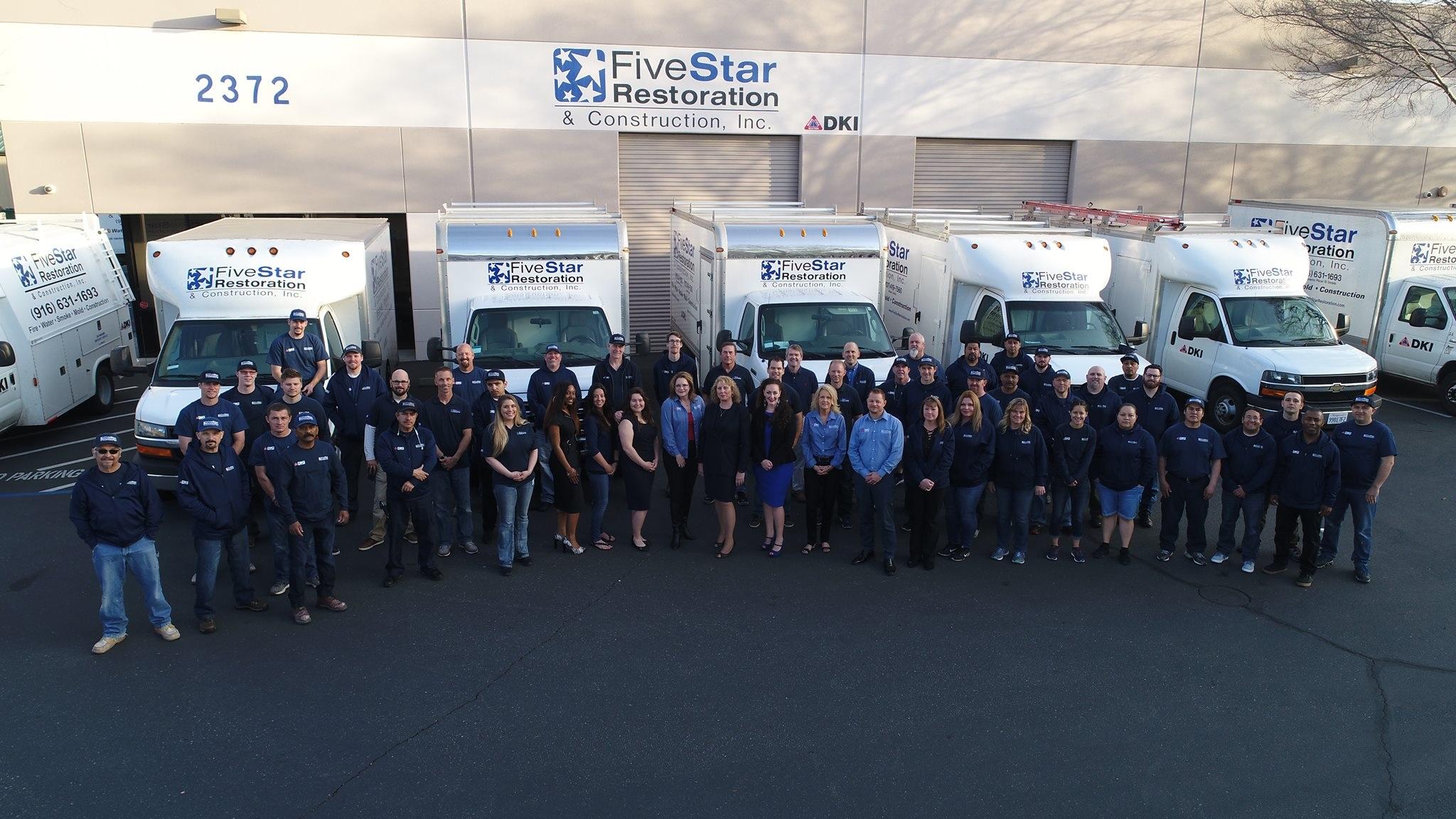 Five Star Restoration employees standing in front of service vans fleet