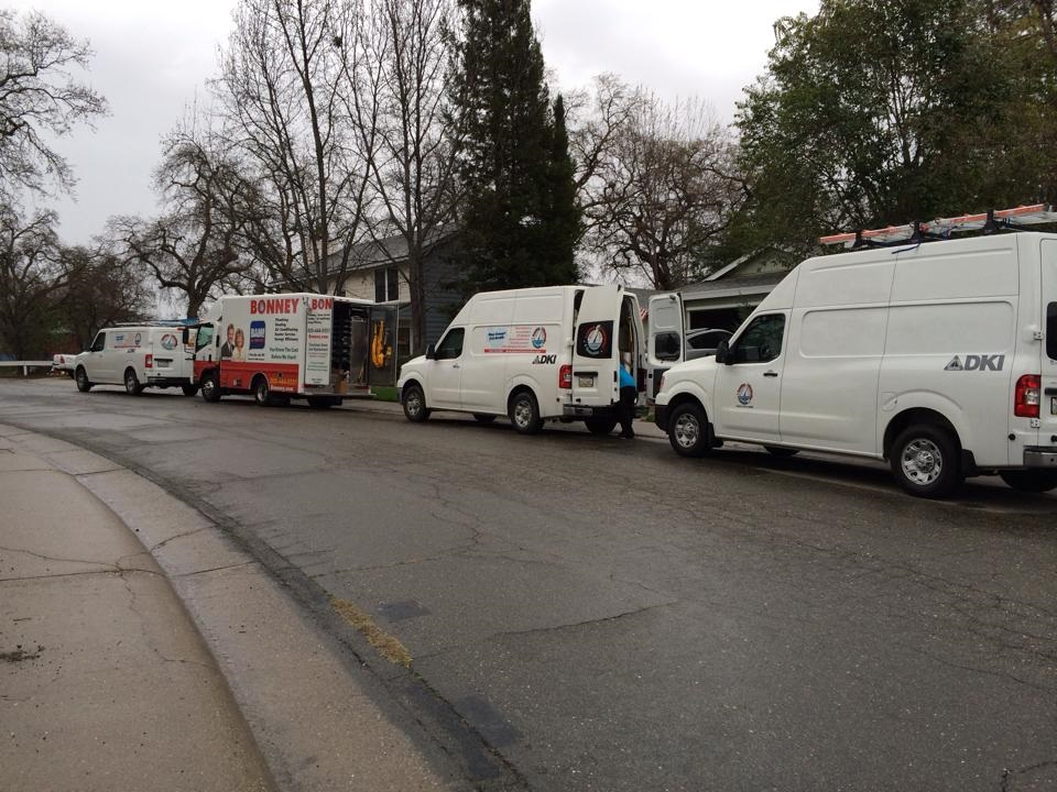 Fleet of DKI service trucks in front of a home