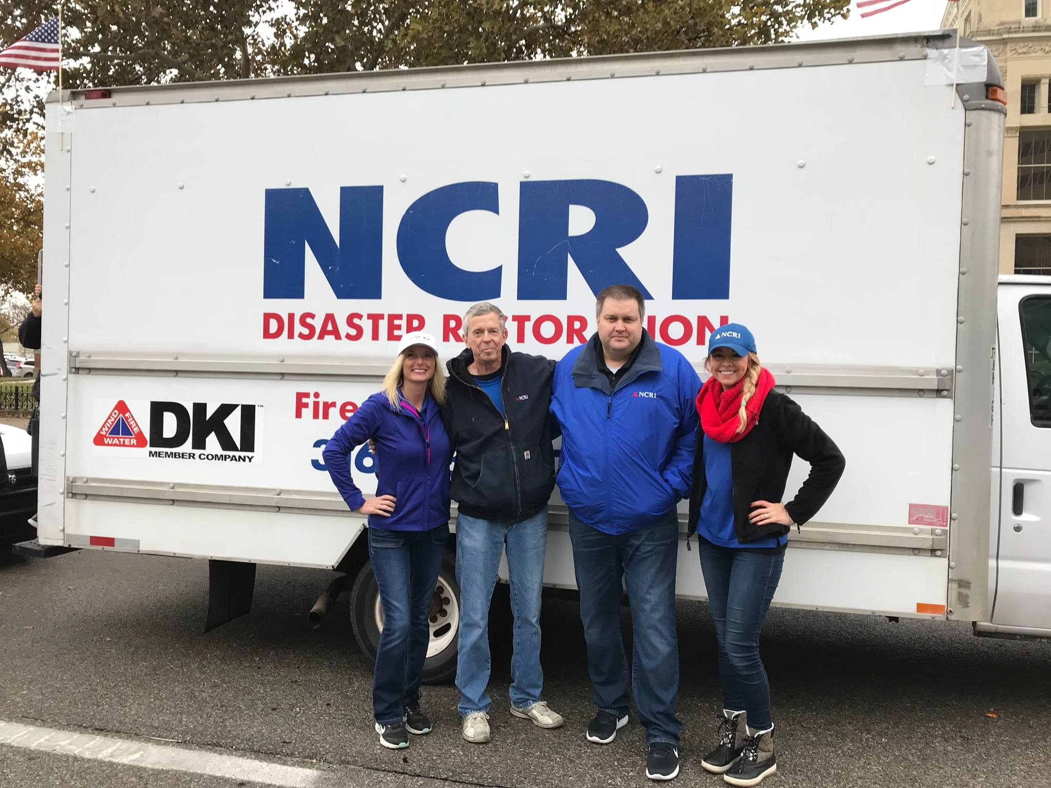 4 NCRI Disaster Restoration employees pose for a picture in front of service truck