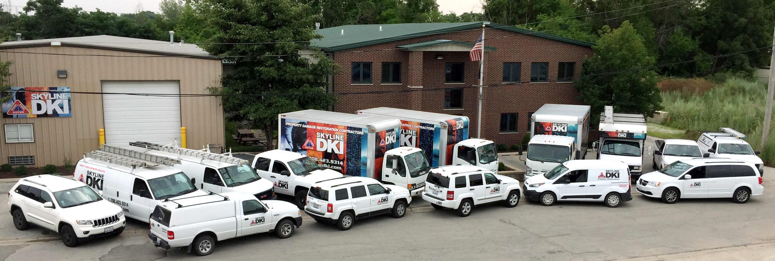 DKI fleet of service vans, trucks and cars out front of a DKI business location