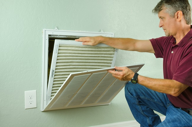 Man checking his air filter in his home