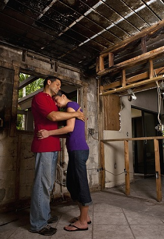 A couple standing in a damaged bare frame home