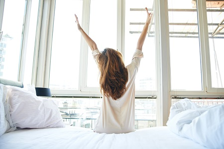 Woman stretching and getting out of bed