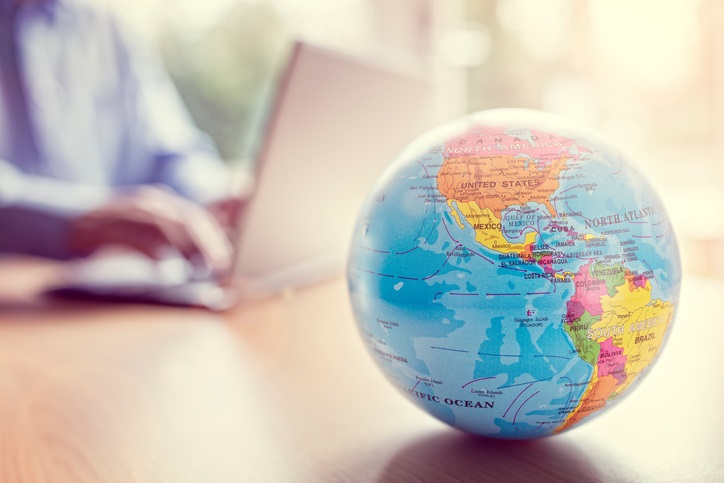 Close up of a plastic globe with a person on their laptop in background