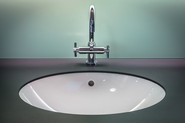 Sink with dark counters and blue-green wall