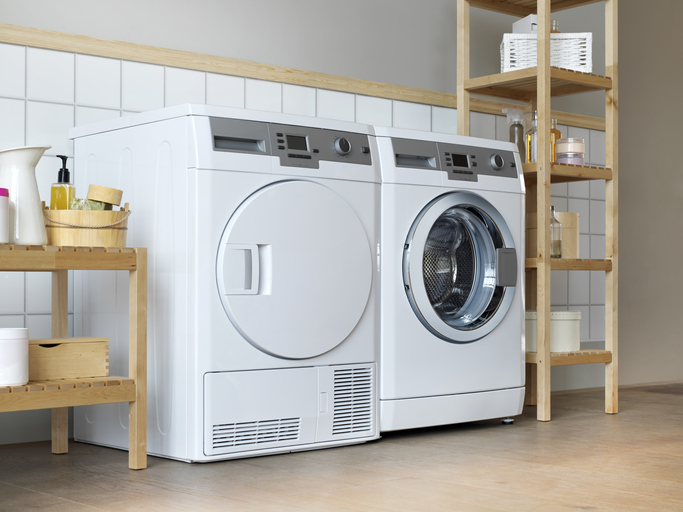 Washer and dryer in home surrounded by shelves