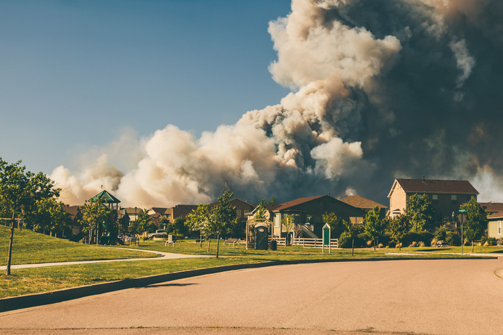 Smoke billowing out of a home in a neighborhood