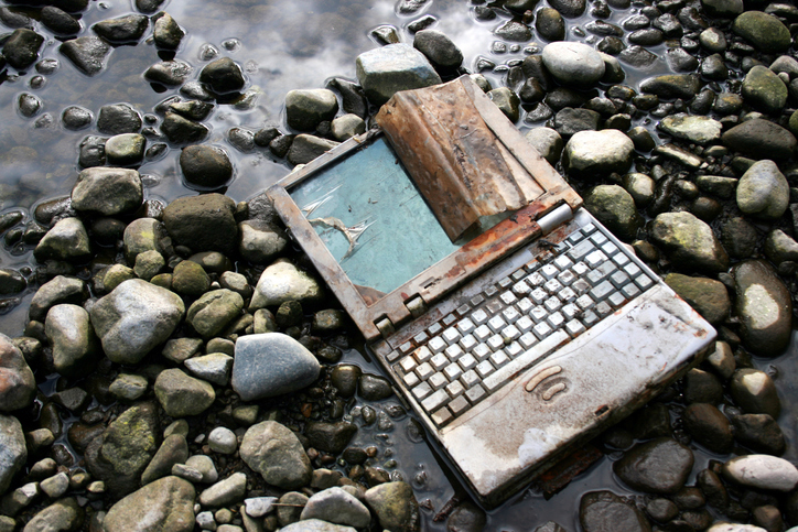 Destroyed laptop laying in the water and on top of rocks