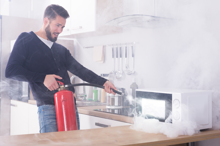 Man extinguishing a microwave with smoke coming out of it