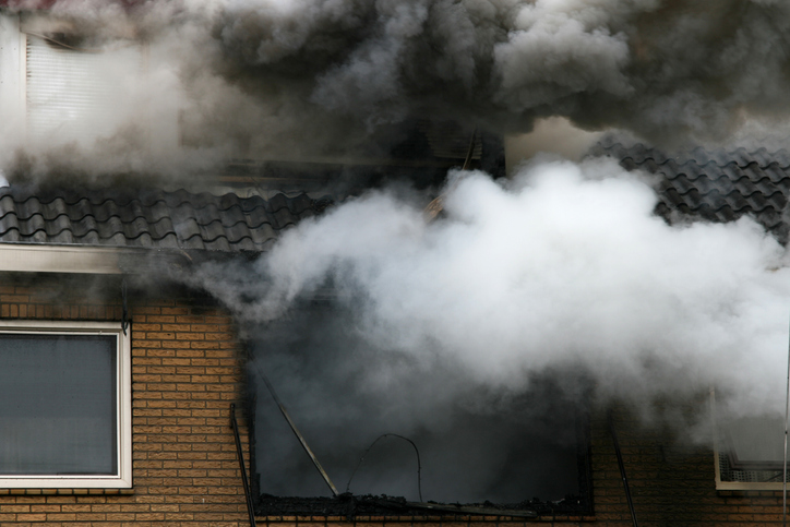 Picture of a house consumed in smoke and fire