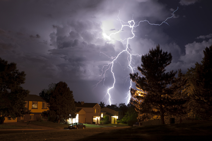 Lightning bolt and thunderhead storms over Denver neighborhood homes