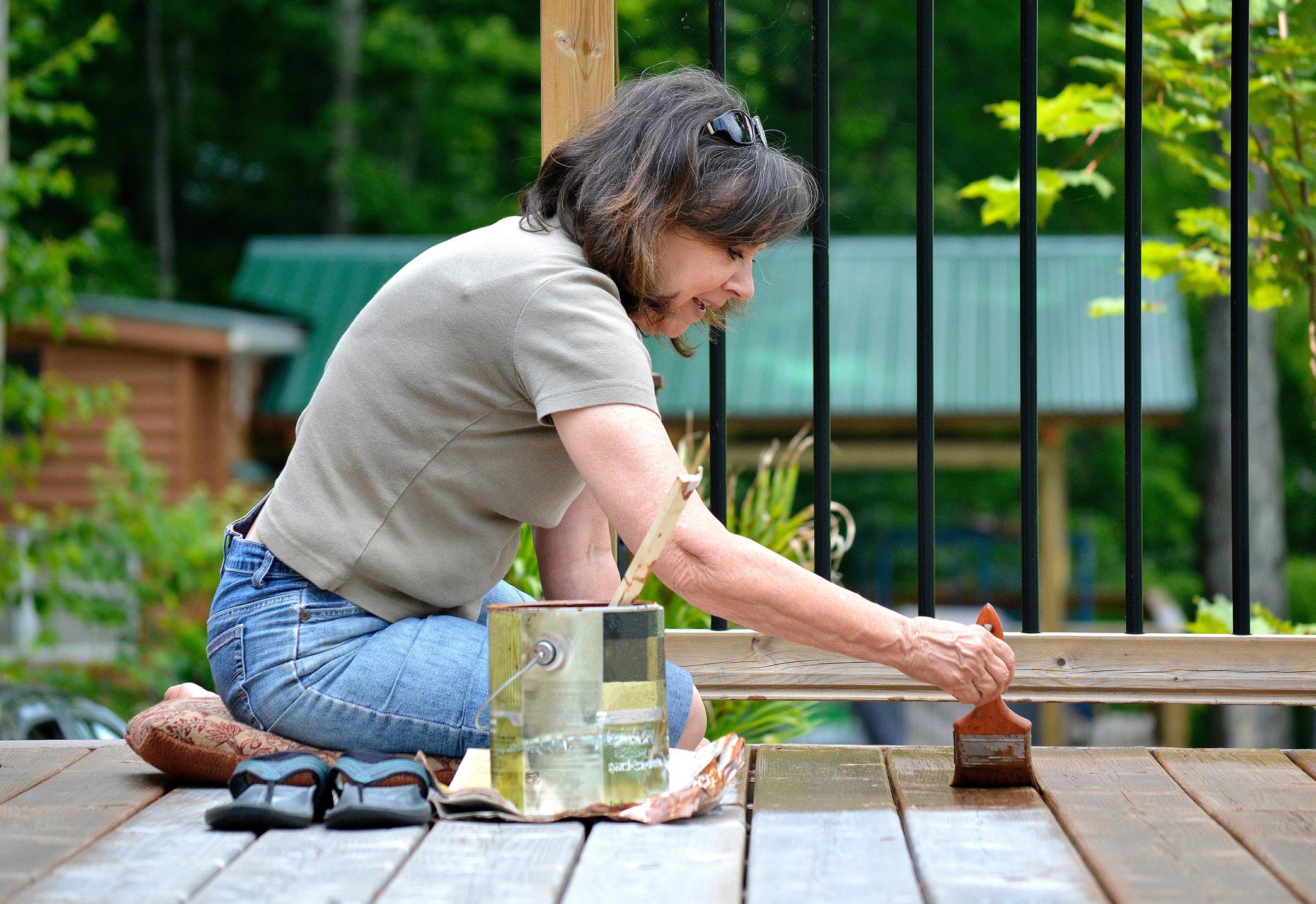 Lifestyle, Senior woman, 50+, paints a deck.